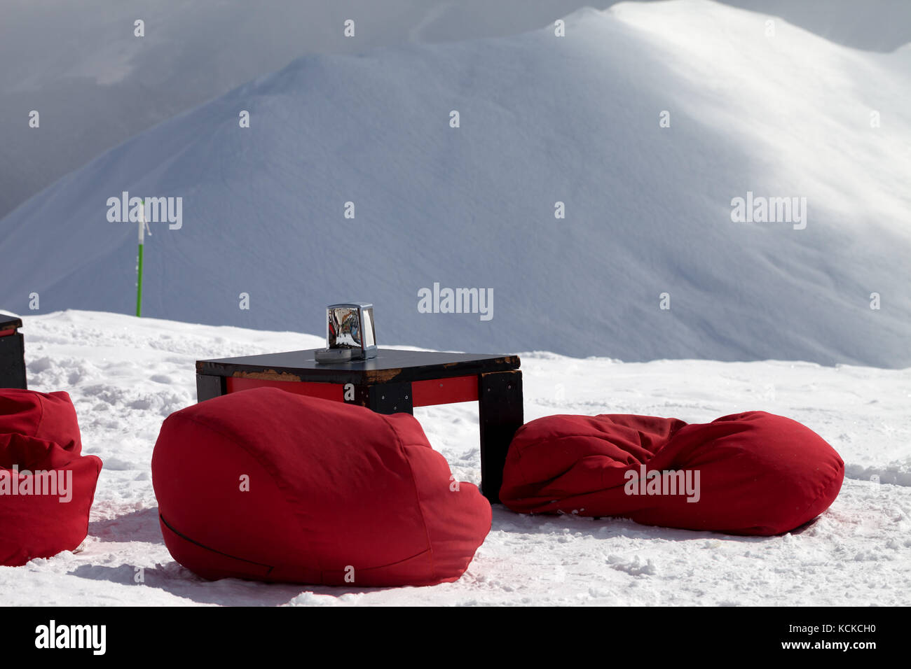 Red bean bag chairs and old table in outdoor cafe at ski resort and snow slope for freeriding at background. Caucasus - Stock Image