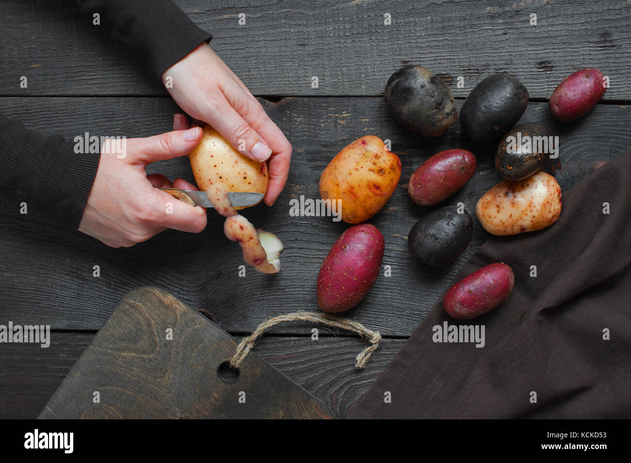Female hands peel the fresh potatoes - Stock Image