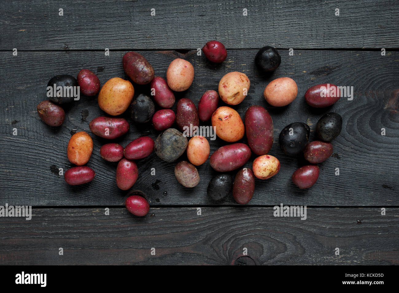 Fresh colorful potatoes on the old wooden table - Stock Image