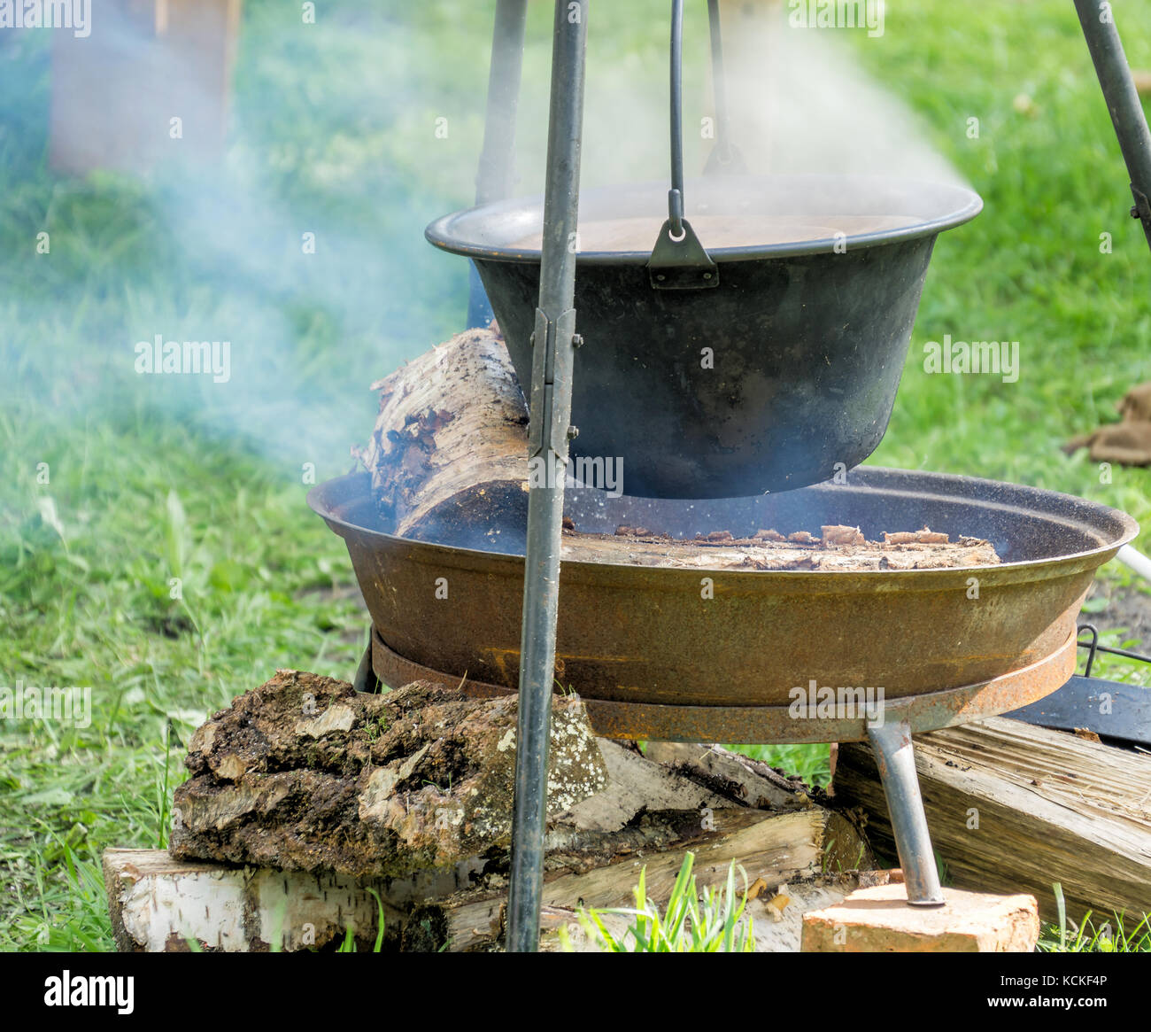 Pot with lunch over open fire place at a medieval festival - Stock Image