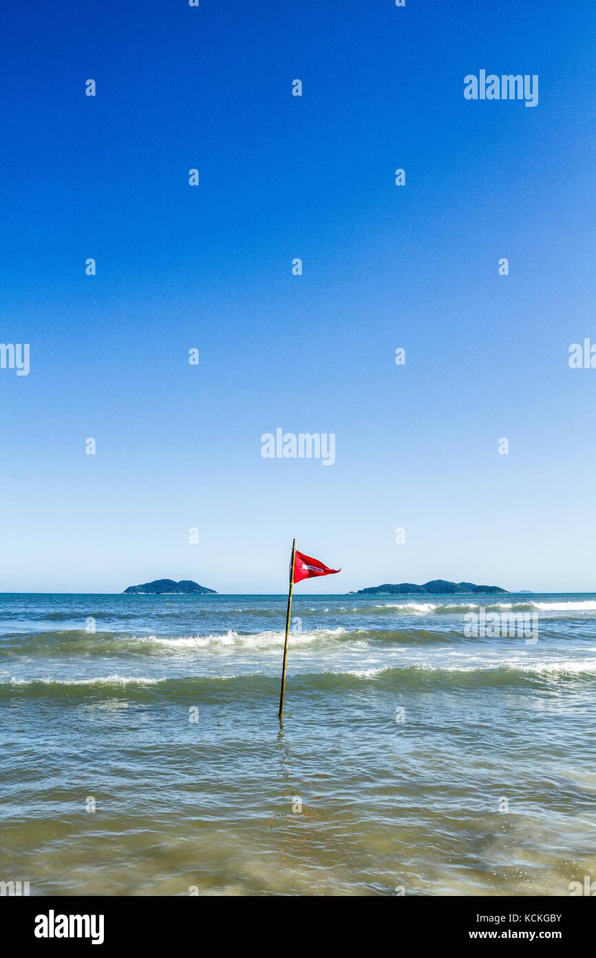 Dangerous conditions sign at Acores Beach. Florianopolis, Santa Catarina, Brazil. - Stock Image