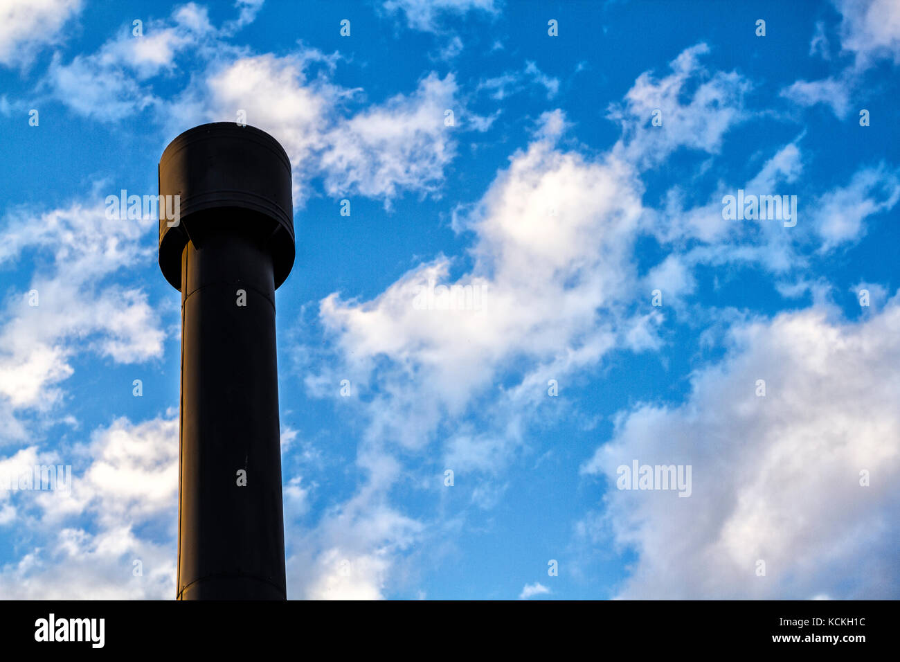 Low angle view of a black chimney against blue sky with some clouds. - Stock Image