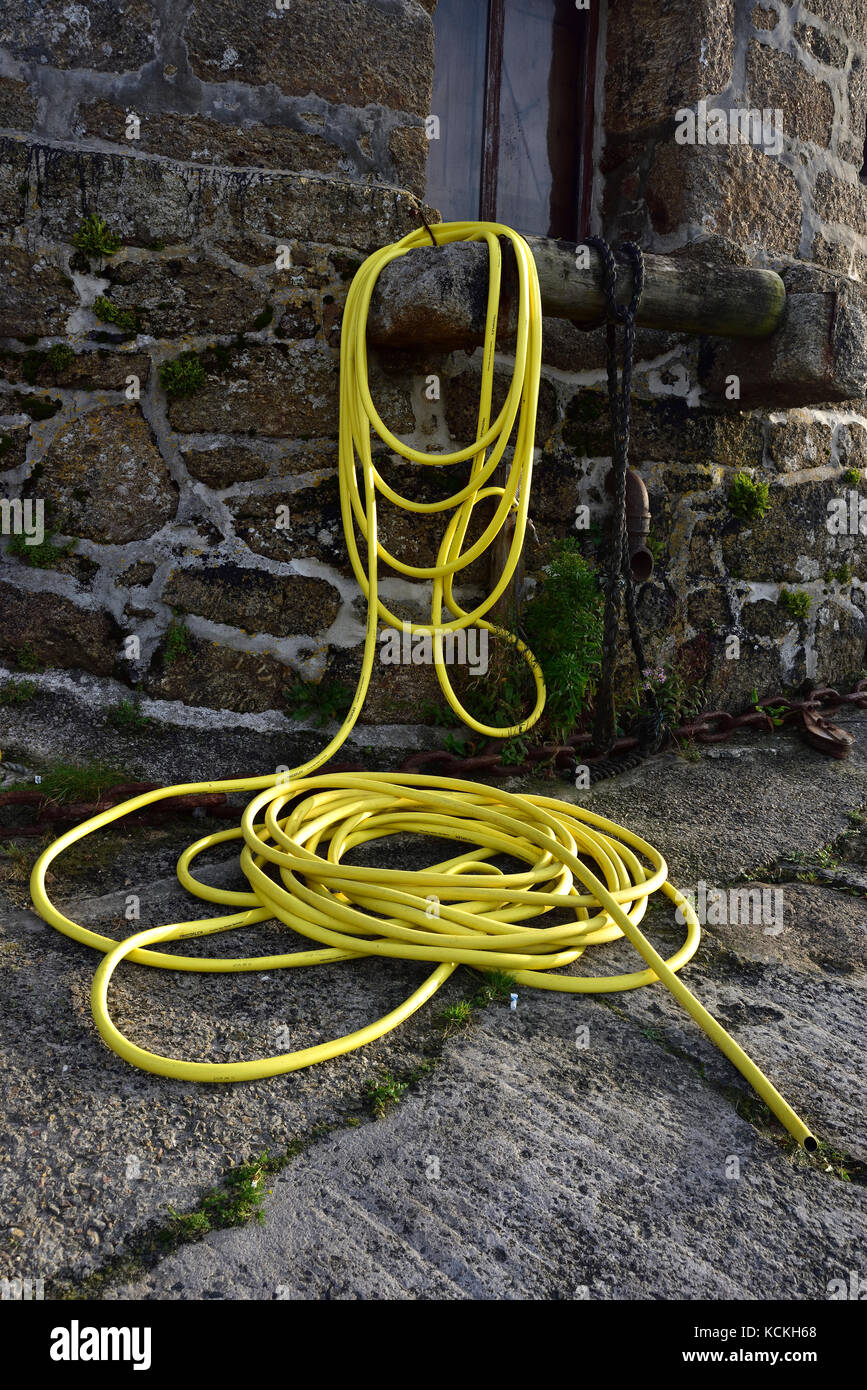 Yellow hosepipe at the harbour, Sennen Cove, Cornwall - Stock Image