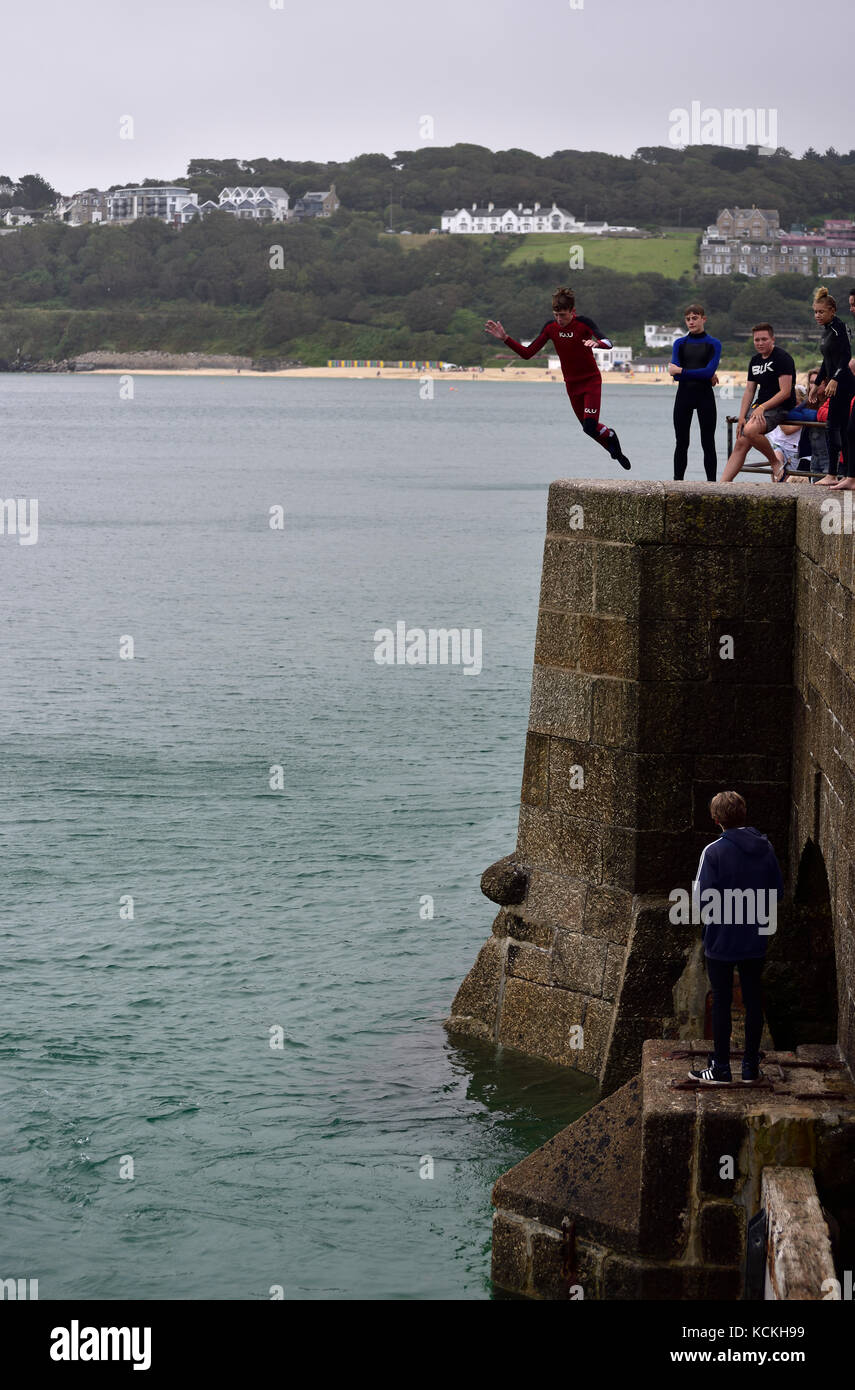 A young man jumping off the pier in St Ives harbour, Cornwall Stock Photo