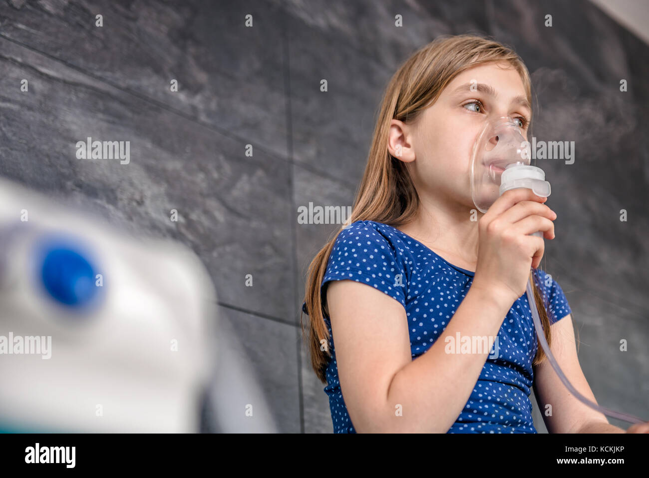 Little girl having a medical inhalation treatment with a nebulizer at the hospital - Stock Image
