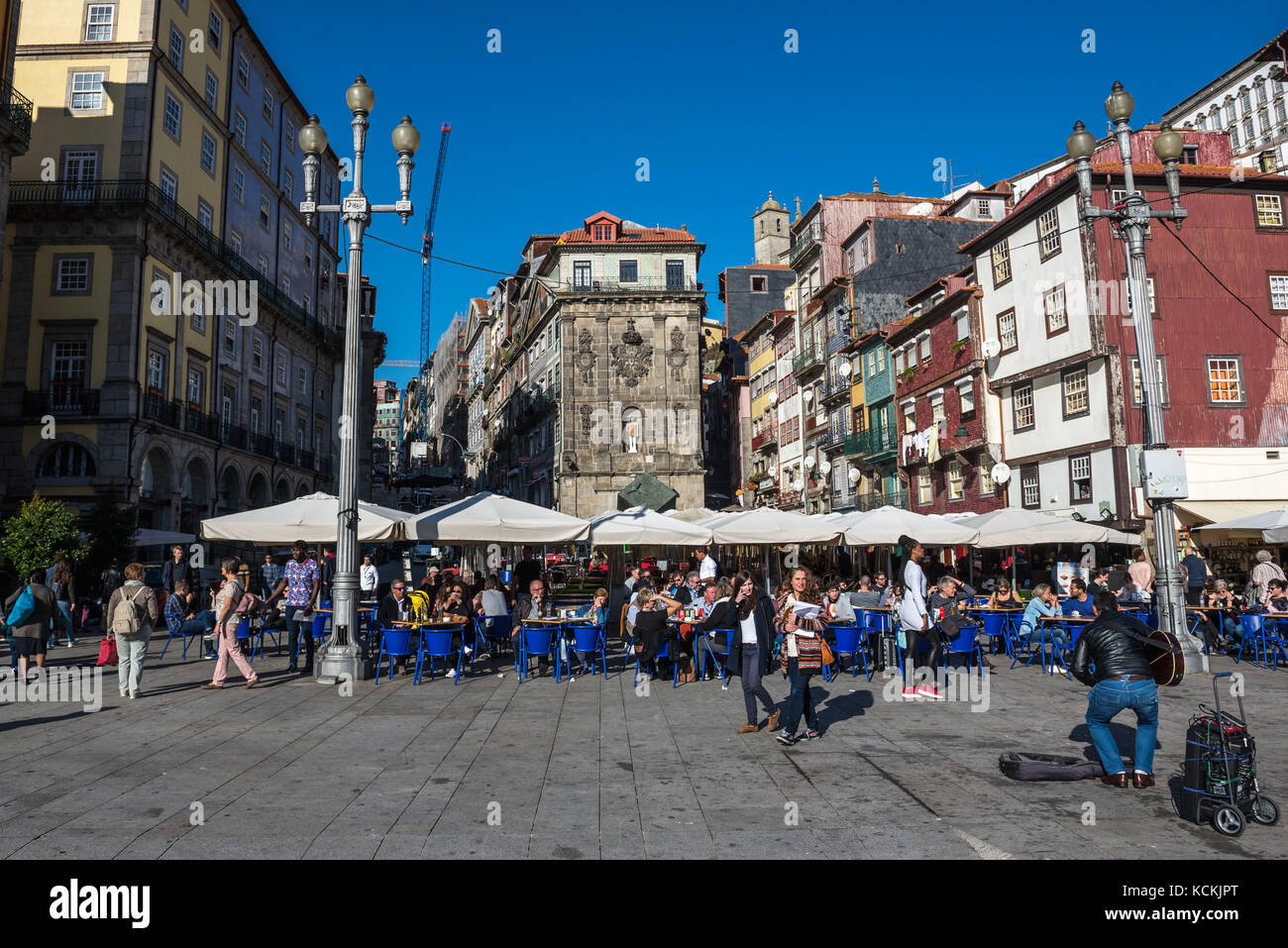 Restaurants and monumental fountain (Fonte da Ribeira) with a St John the Baptist statue on Ribeira Square in Porto - Stock Image