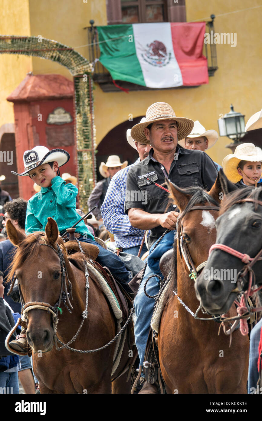 Mexican cowboys ride through the Jardin Allende at the end of their pilgrimage during the festival of Saint Michael - Stock Image
