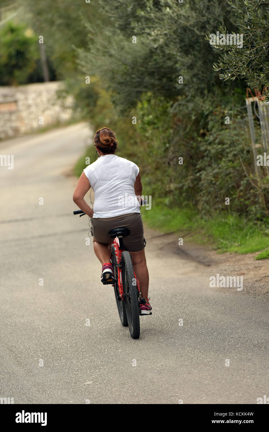a woman riding a bicycle away from canera wearing a rucksack pedalling. - Stock Image