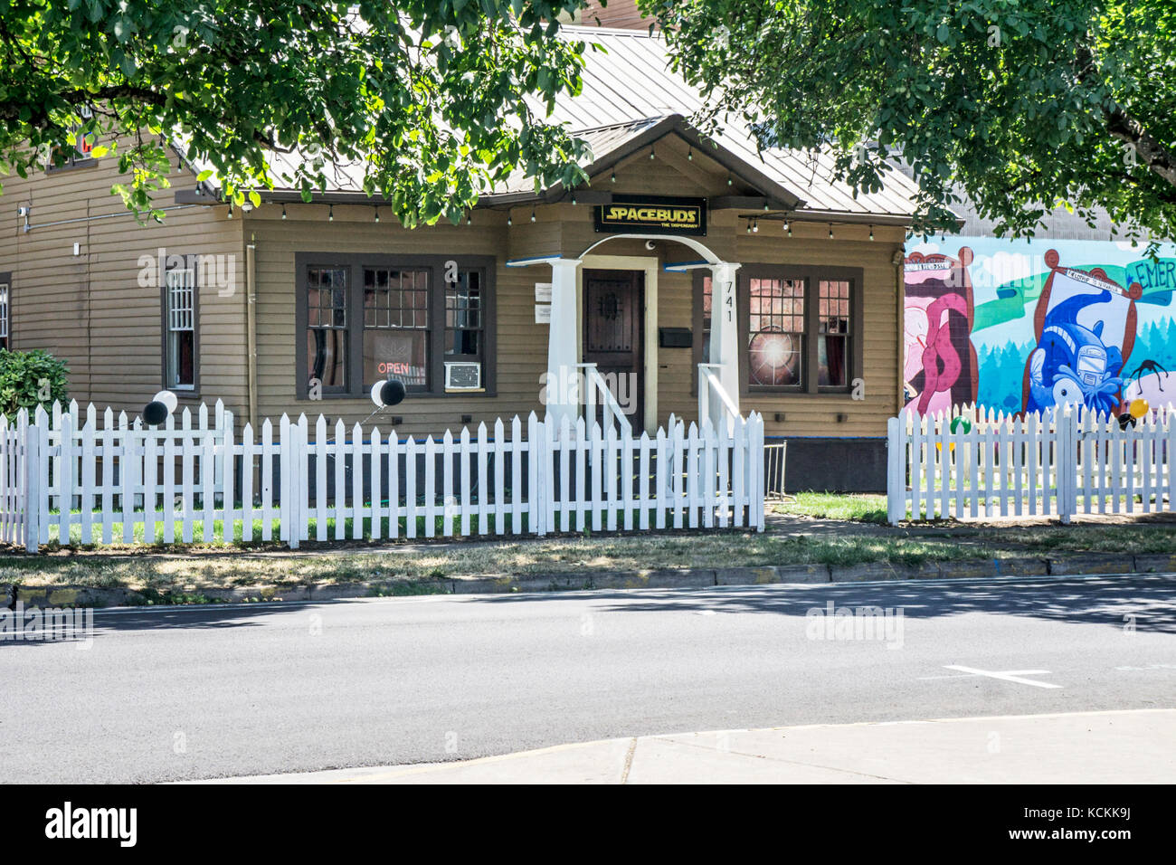 20's clapboard cottage with white picket fence, old shade trees serves as retail medical & recreational marijuana Stock Photo
