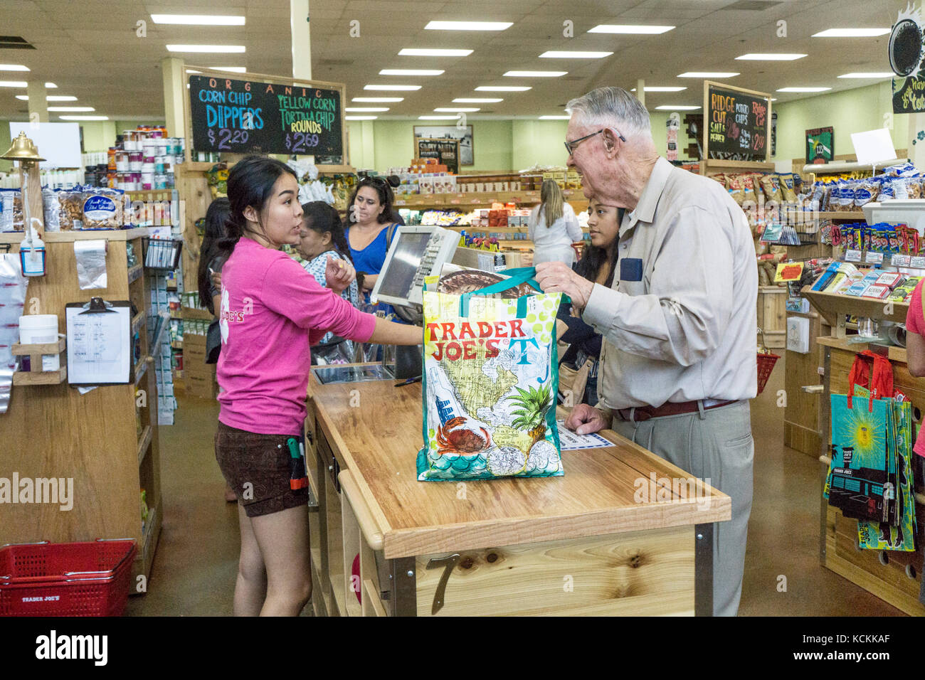 tall smiling elderly man at supermarket checkout stops briefly for  pleasant word with pretty young Asian cashier - Stock Image