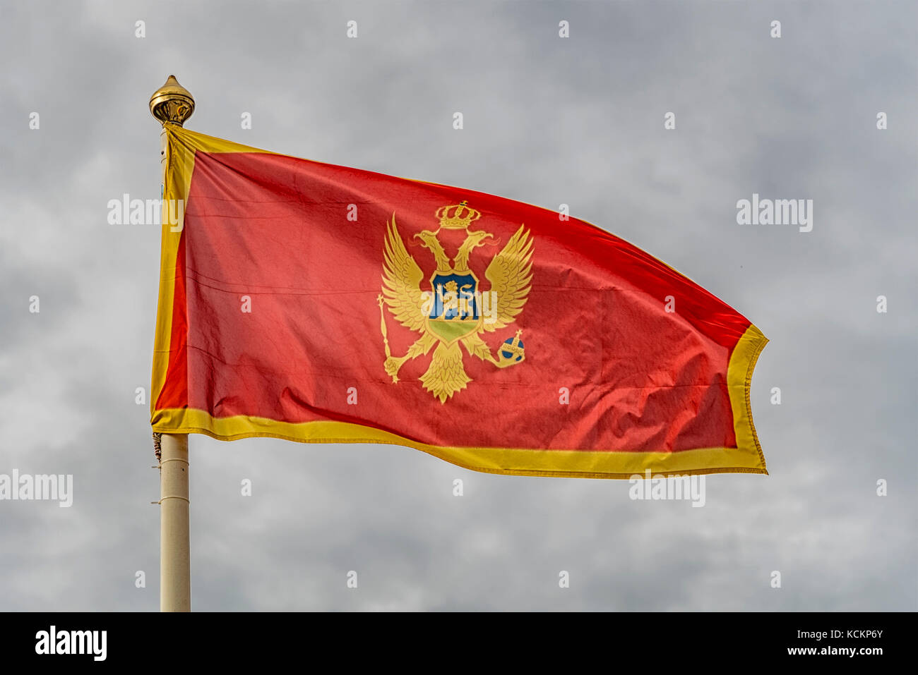The flag of Montenegro fluttering in the wind against a cloudy sky background. Stock Photo