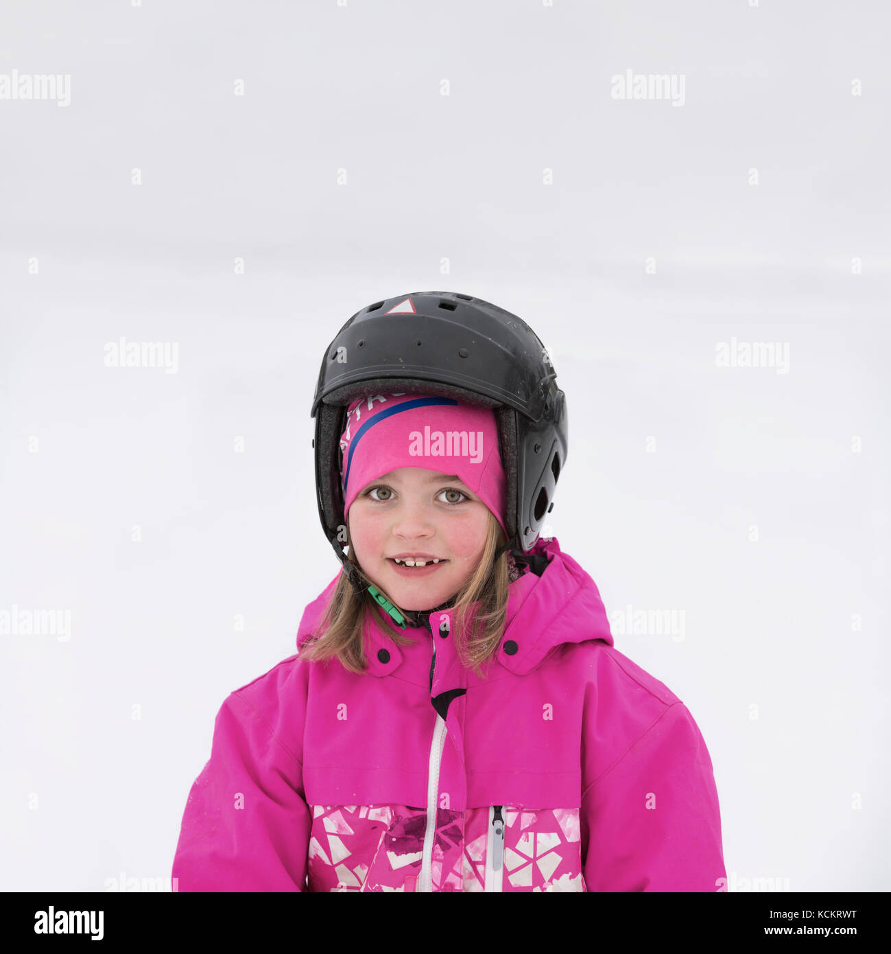 Eye contact portrait of young smiling girl with helmet in the snow outdoors - Stock Image