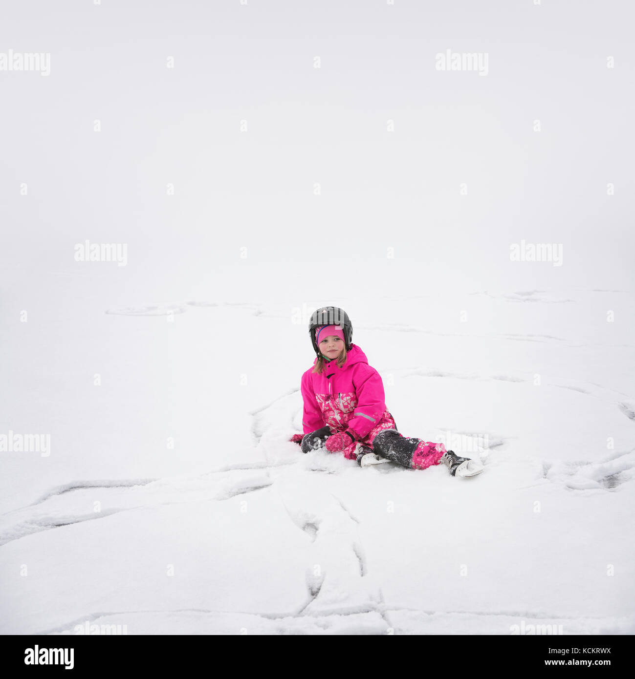 Young ice skating girl with helmet sitting in the snow on the ice after a fall - Stock Image