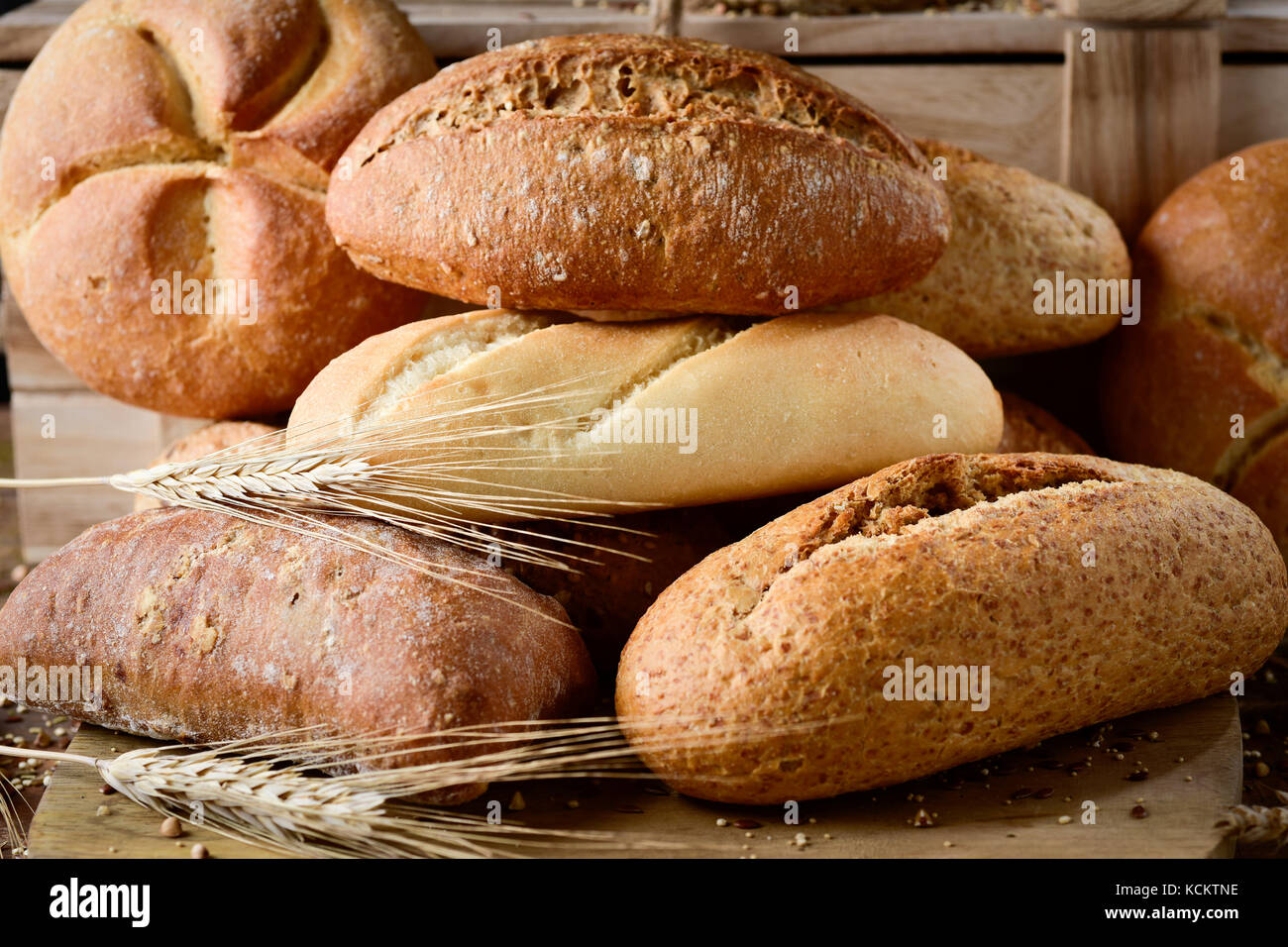 closeup of an assortment of different bread rolls and some wheat ears on a rustic wooden table - Stock Image