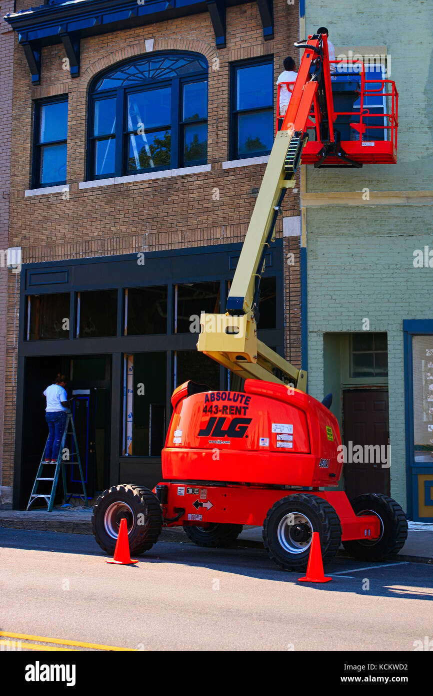 Men using a cherry picker to paint the exterior of a store in downtown Lebanon Tn, USA - Stock Image