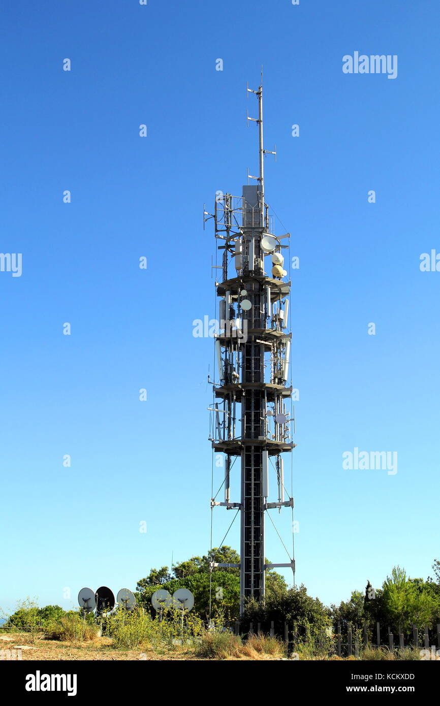 Modern mobile phone, or cellphone, communications mast or tower, with carious aerials and satellite dishes and receivers - Stock Image