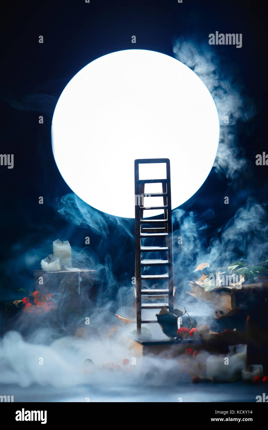 Ladder to the Moon. Conceptual still life wih smoke, night scene with candles and books. Dark still life with copy - Stock Image