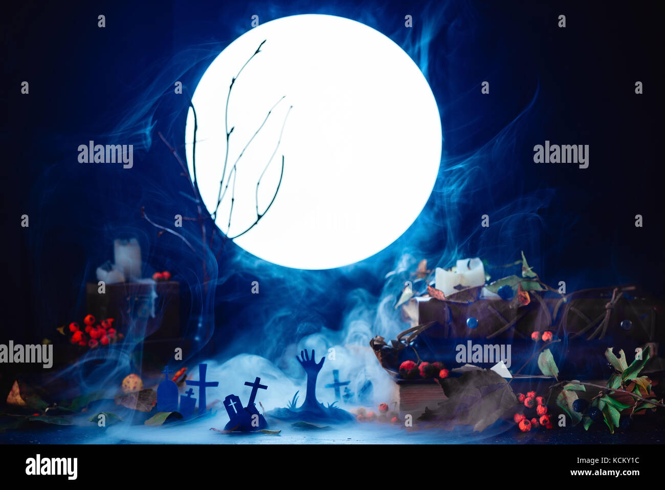 Graveyard with rising zombies silhouettes in full moon light. Conceptual Halloween still life with smoke, dry branches, - Stock Image