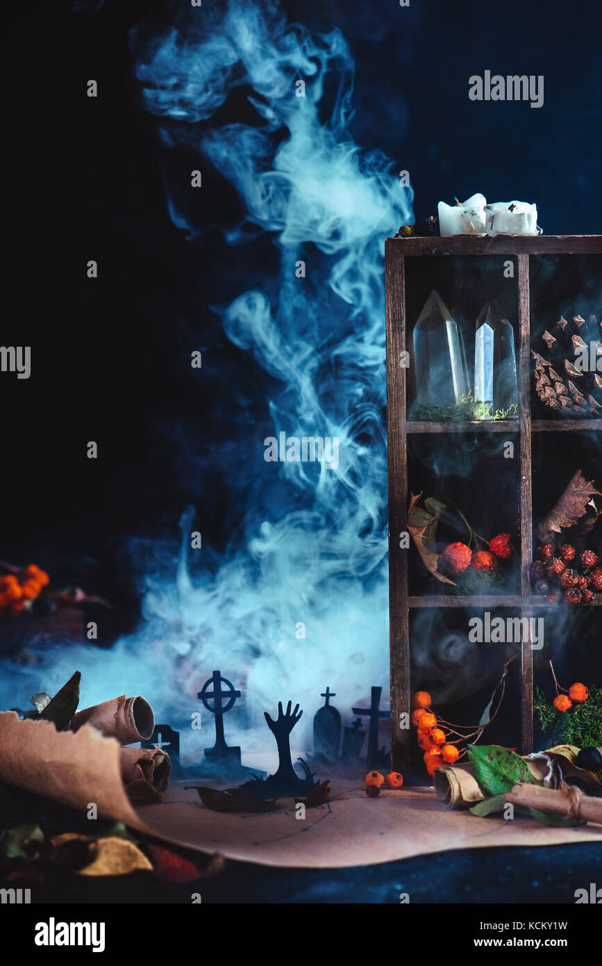 Moonlight graveyard with rising zombies silhouettes in conceptual Halloween still life with smoke, wirards workplace, - Stock Image