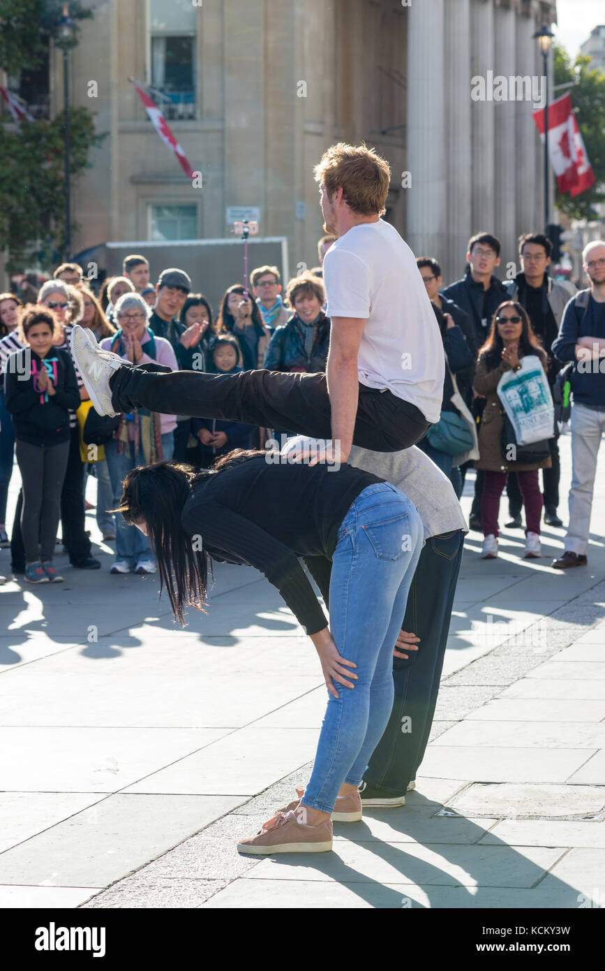 Street performer entertaining crowds in Trafalgar Square, London, England, UK, with some audience participation - Stock Image