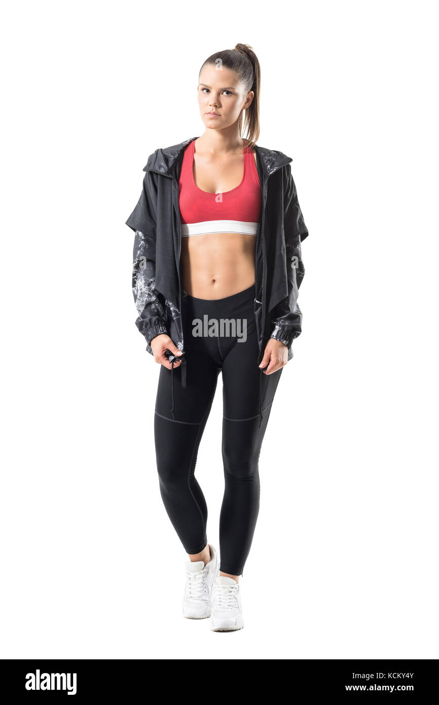 Beautiful fit active woman with perfect abs posing in sportswear with tracksuit jacket. Full body length portrait - Stock Image