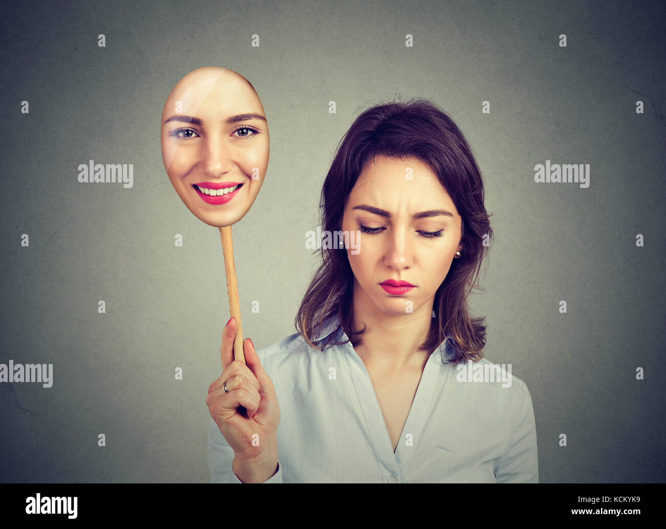 Sad woman looking down taking off happy mask of herself Stock Photo