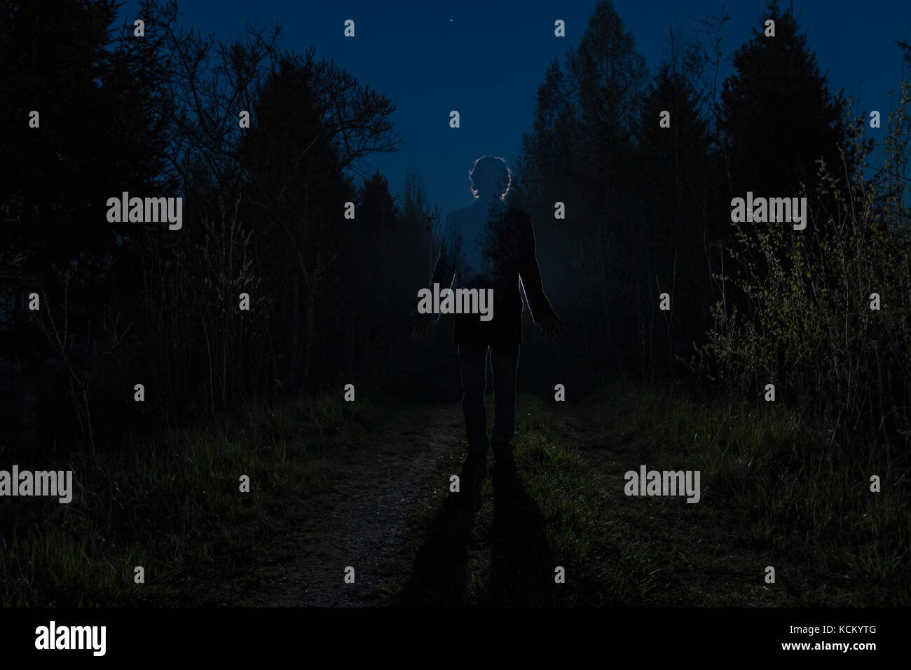 Male silhouette at the dark forest pathway through the bushes in the night. Man standing on the road against the - Stock Image