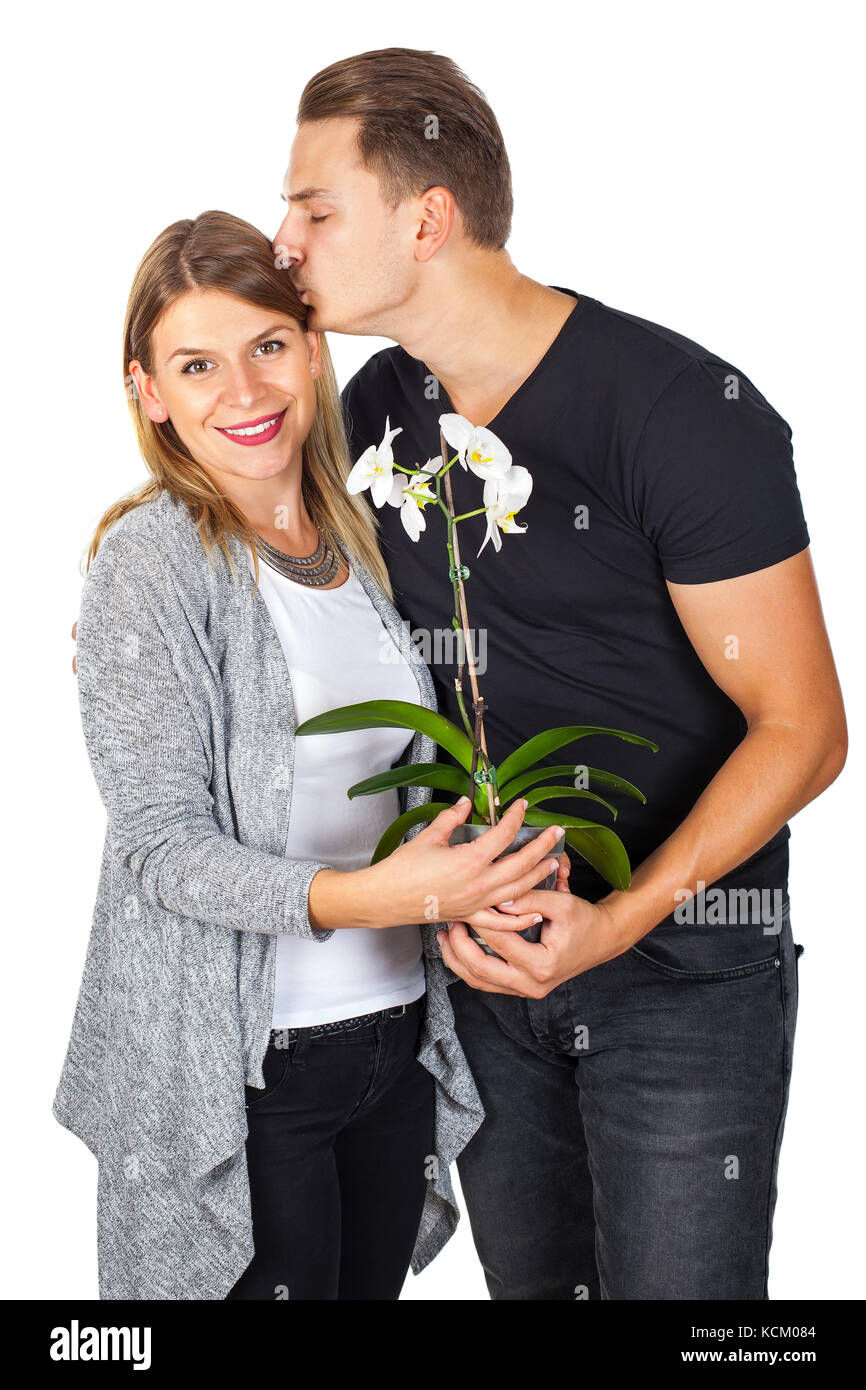 Young man kissing his girlfriend, holding an orchid - anniversary gift, on isolated - Stock Image