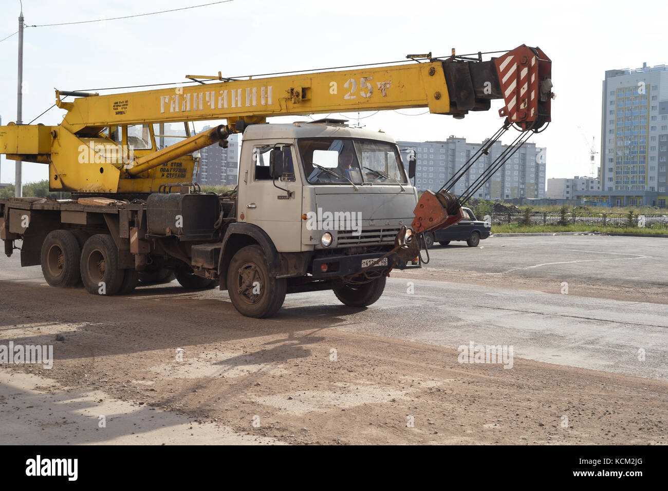 Old aged Kamaz vehicle with crane attachment moves along an empty road in Russia - Stock Image