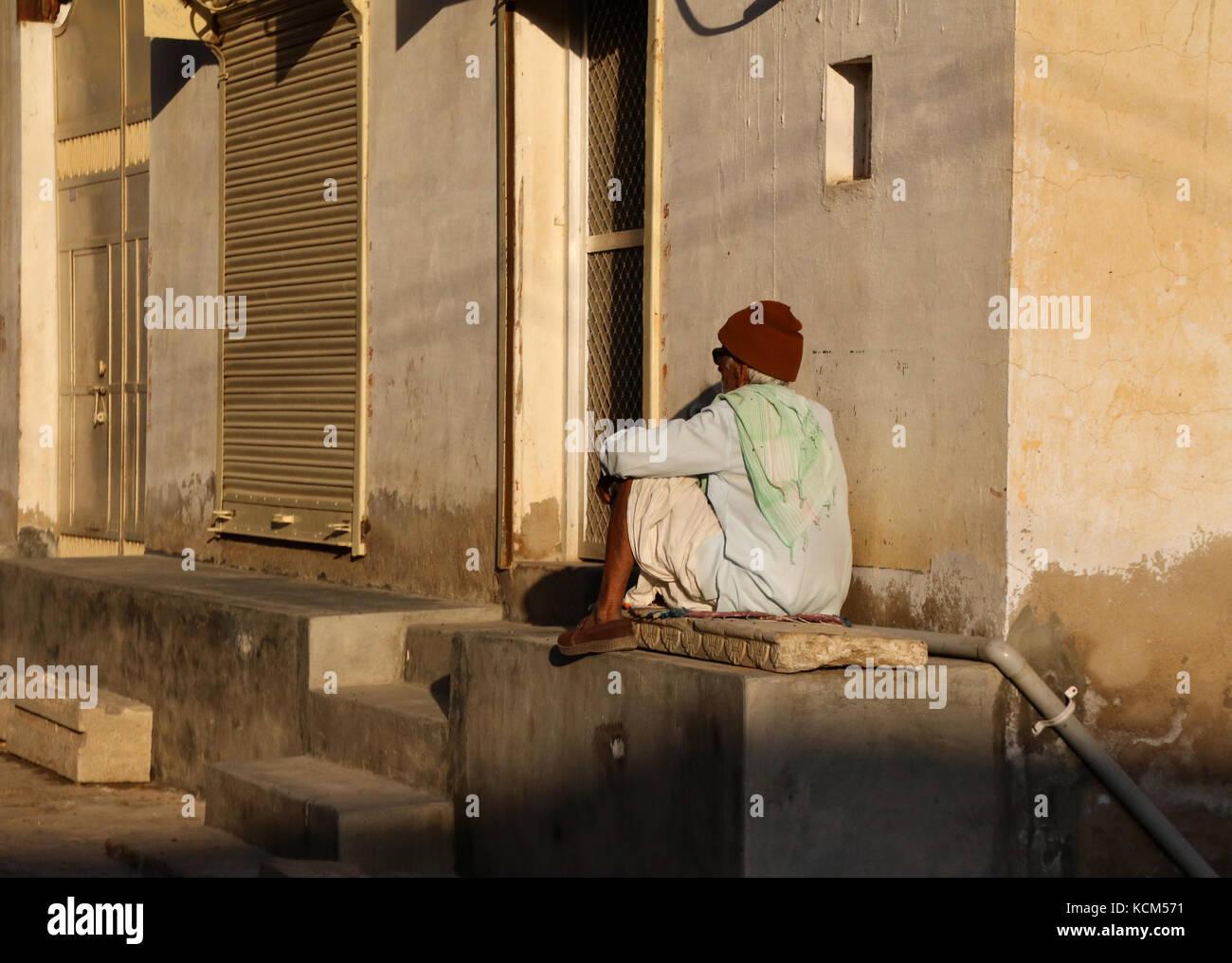 Man sitting on doorstep with back to camera - Stock Image