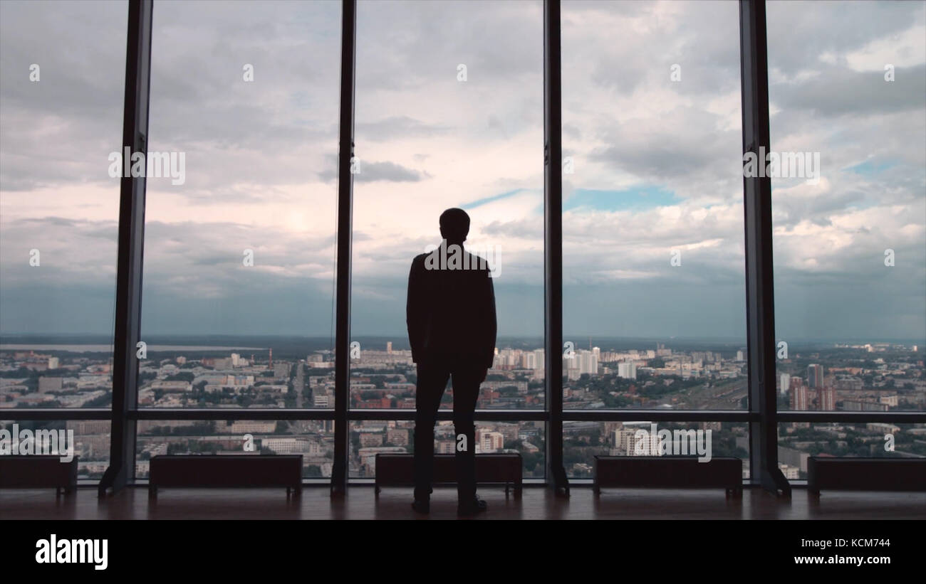 Rear view of businessman in an office with panoramic city view. Businessman admires the city from the panoramic - Stock Image