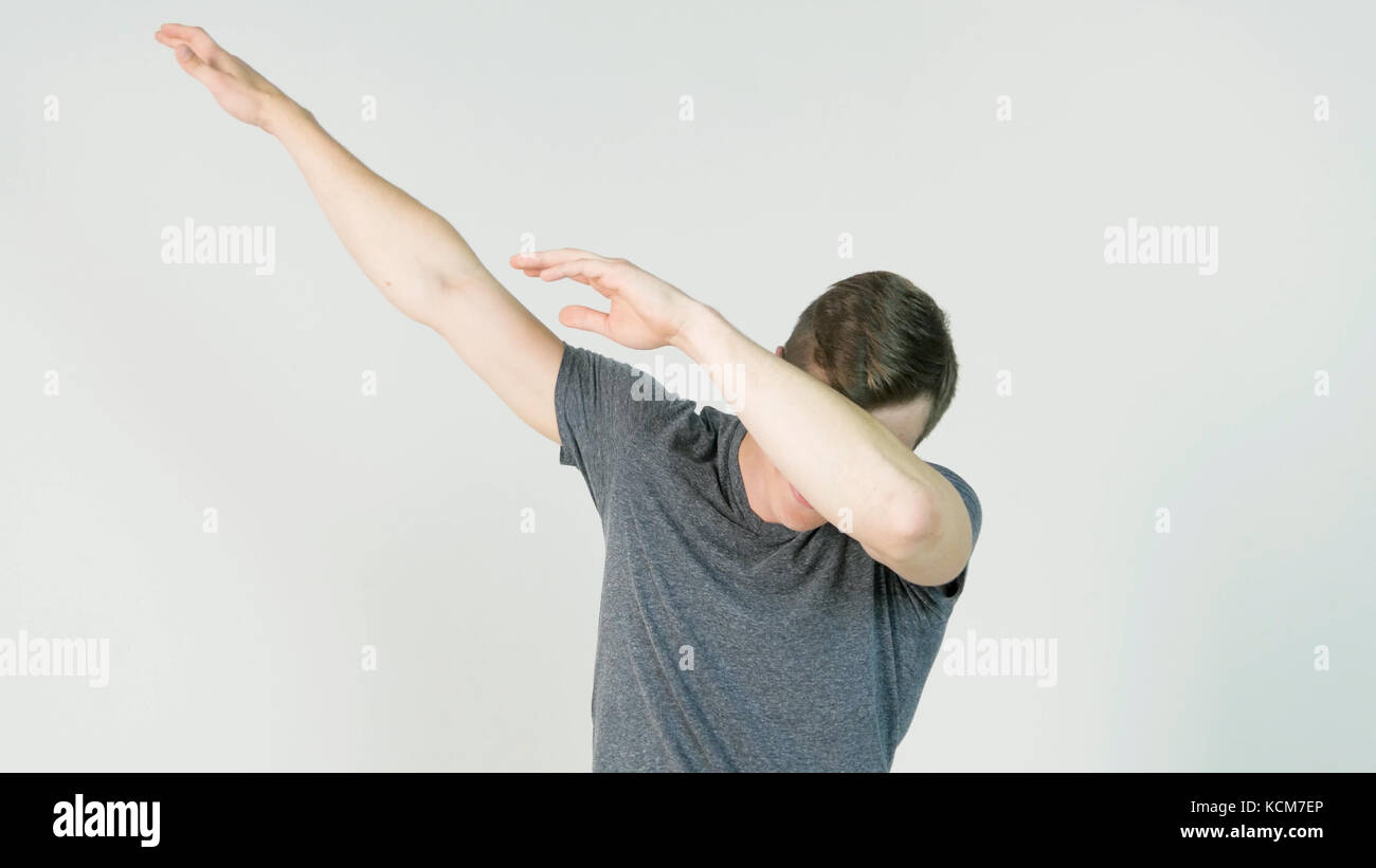 Young man makes a dab or flex it's dance move on white background - Stock Image