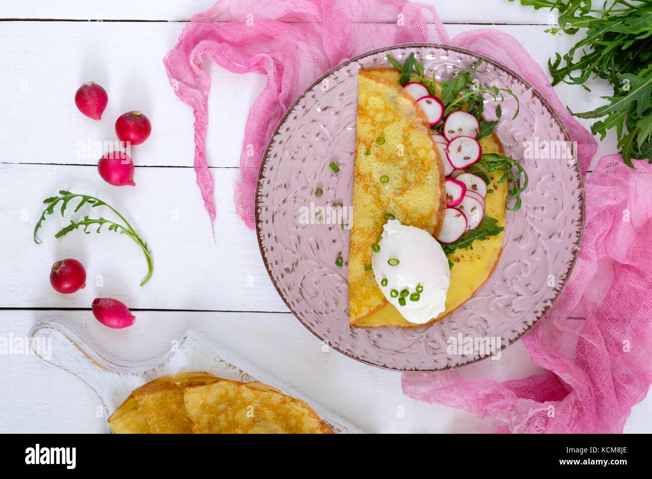 Useful french breakfast: radish salad and arugula, egg poached on a thin crape on a ceramic plate on a white wooden - Stock Image