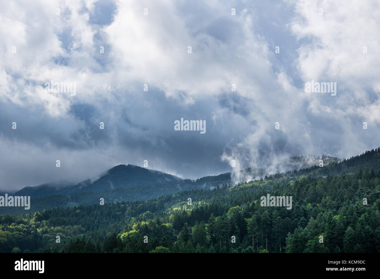 Waft of mist over black forest mountains with sun and rain clouds in autumn - Stock Image