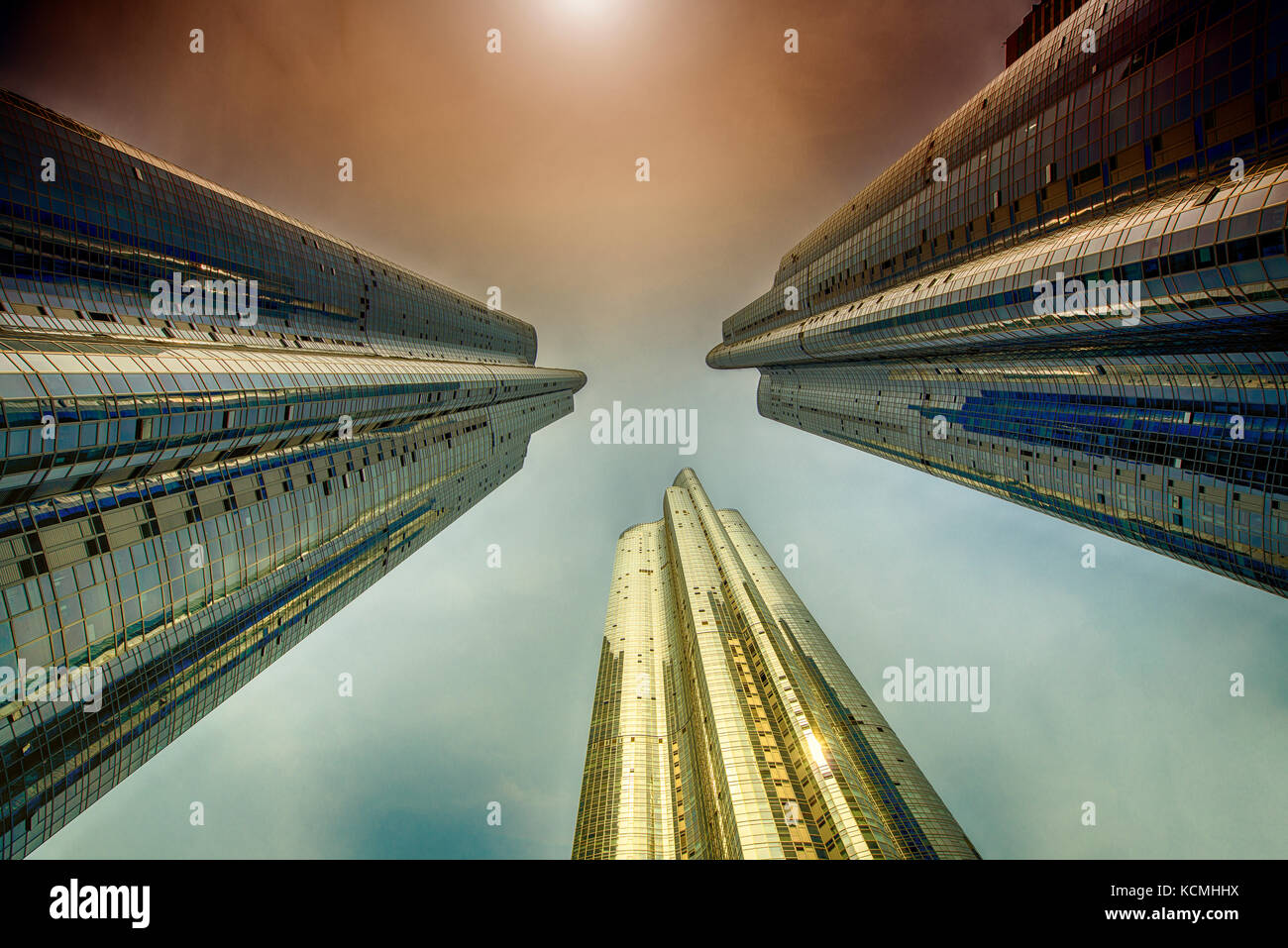 Three sky scrapers looking up into the edge of the sun. - Stock Image