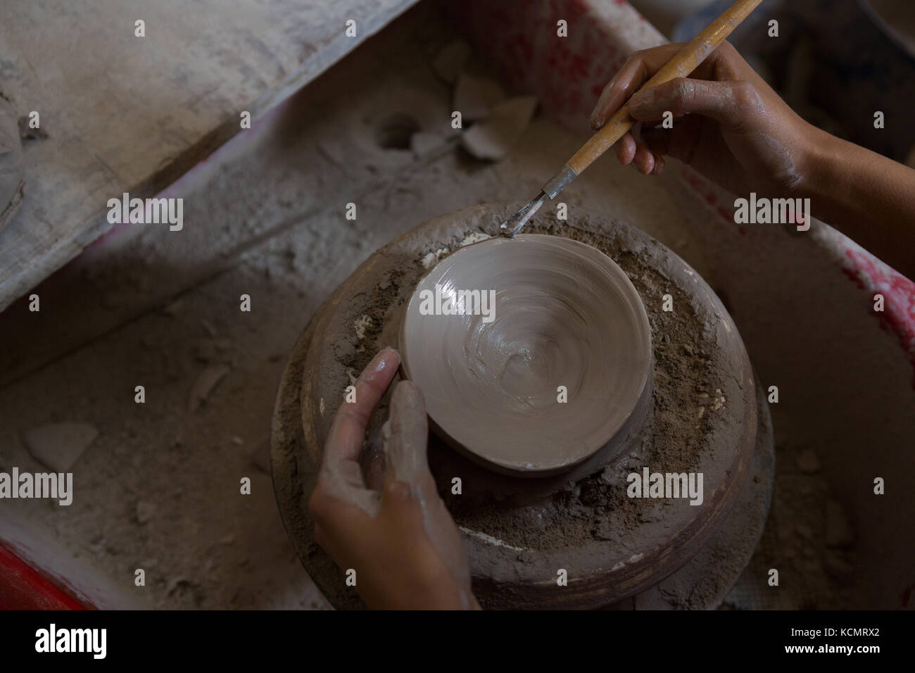 Overhead of female potter molding a bowl with hand tool - Stock Image