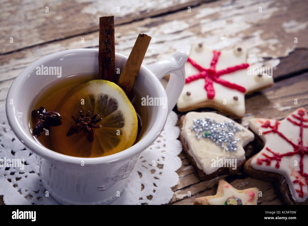 Close-up of tea, spices and cookies on wooden plank - Stock Image