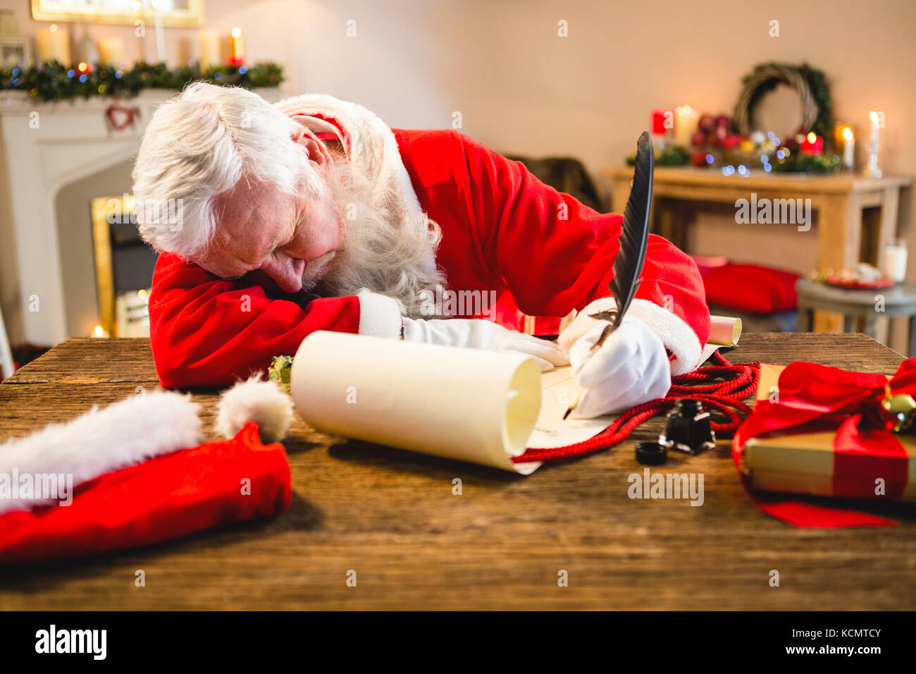 Santa claus sleeping at table while writing a letter with a quill during christmas time - Stock Image