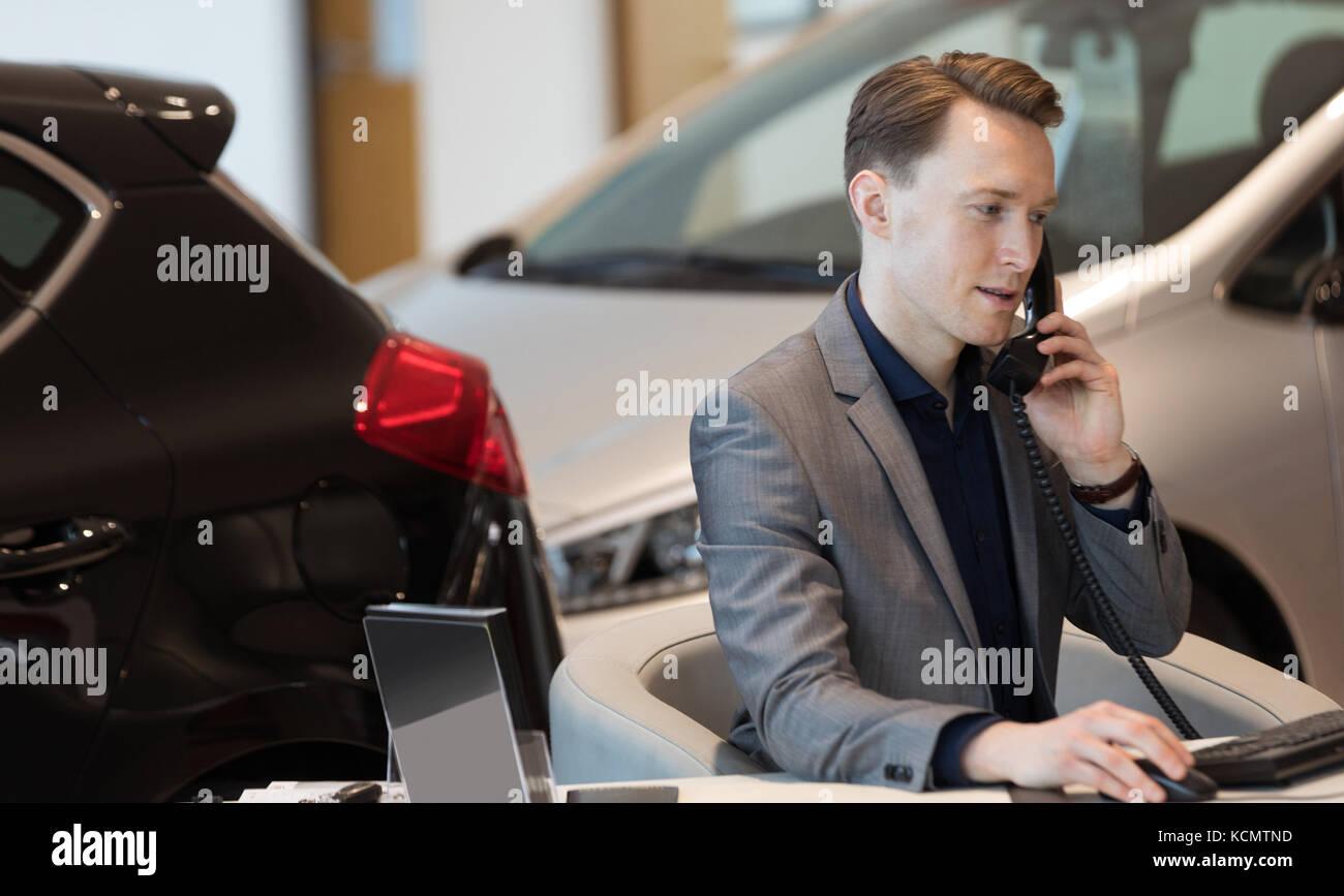 Businessman talking on landline phone while working in showroom - Stock Image