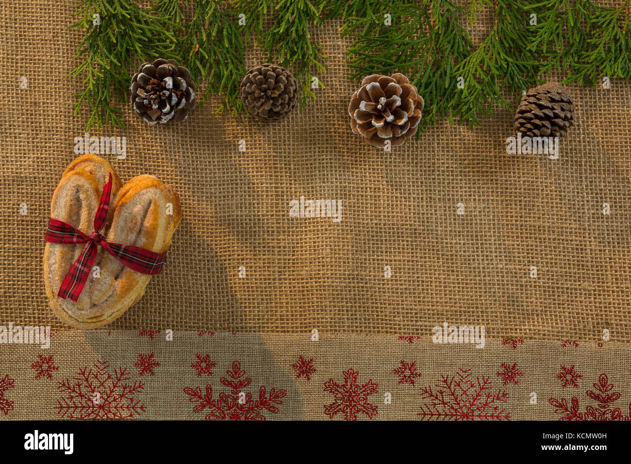 Overhead view of food tied with ribbon by pine cone and twigs on burlap - Stock Image