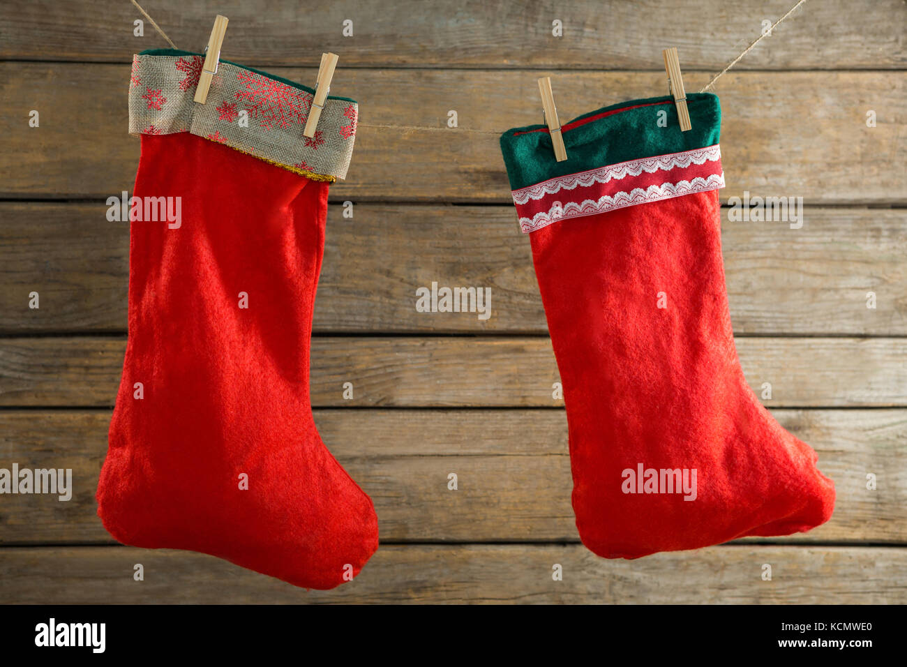 close up of stockings hanging on rope against wooden wall stock image