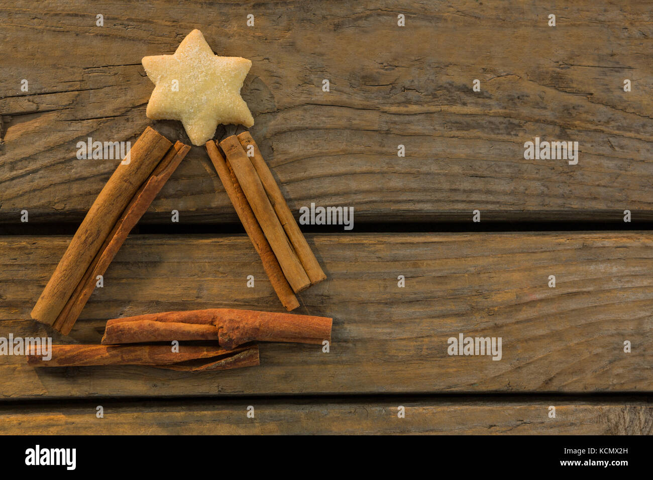 Overhead View Of Star Shape Cookie With Cinnamon Sticks On Wooden
