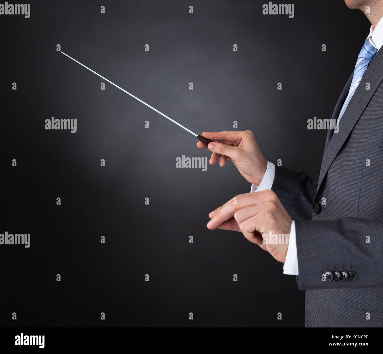 Close-up Of Orchestra Conductor Hands Holding Baton Over Black Background - Stock Image