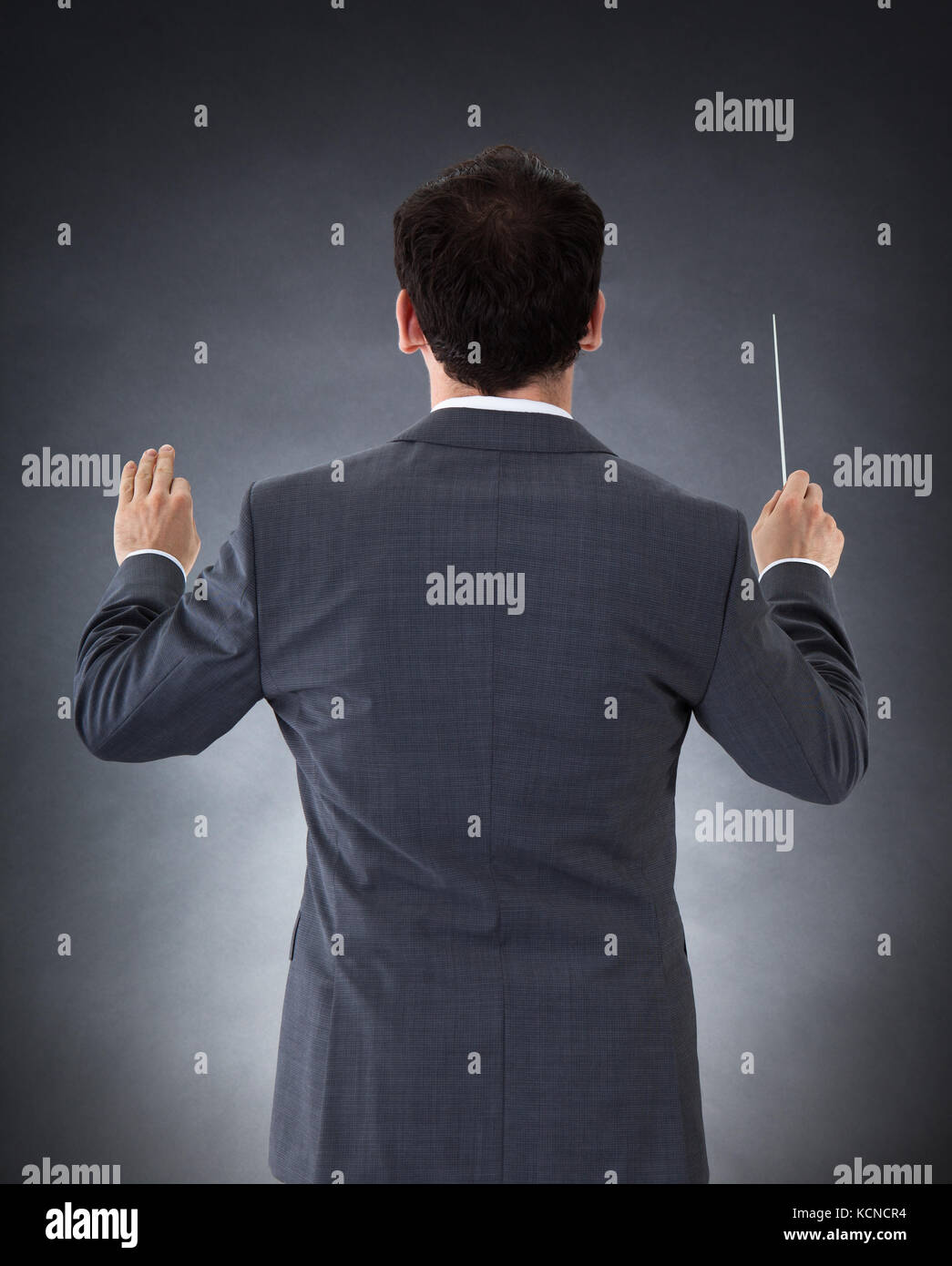 Male Orchestra Conductor Directing With Baton Over Black Background - Stock Image