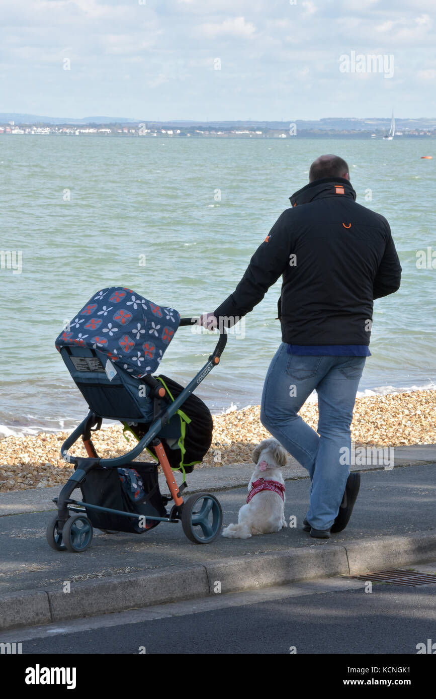 a man standing on the beach or esplanade seafront looking out to sea holding his child in a pushchair on a windy - Stock Image