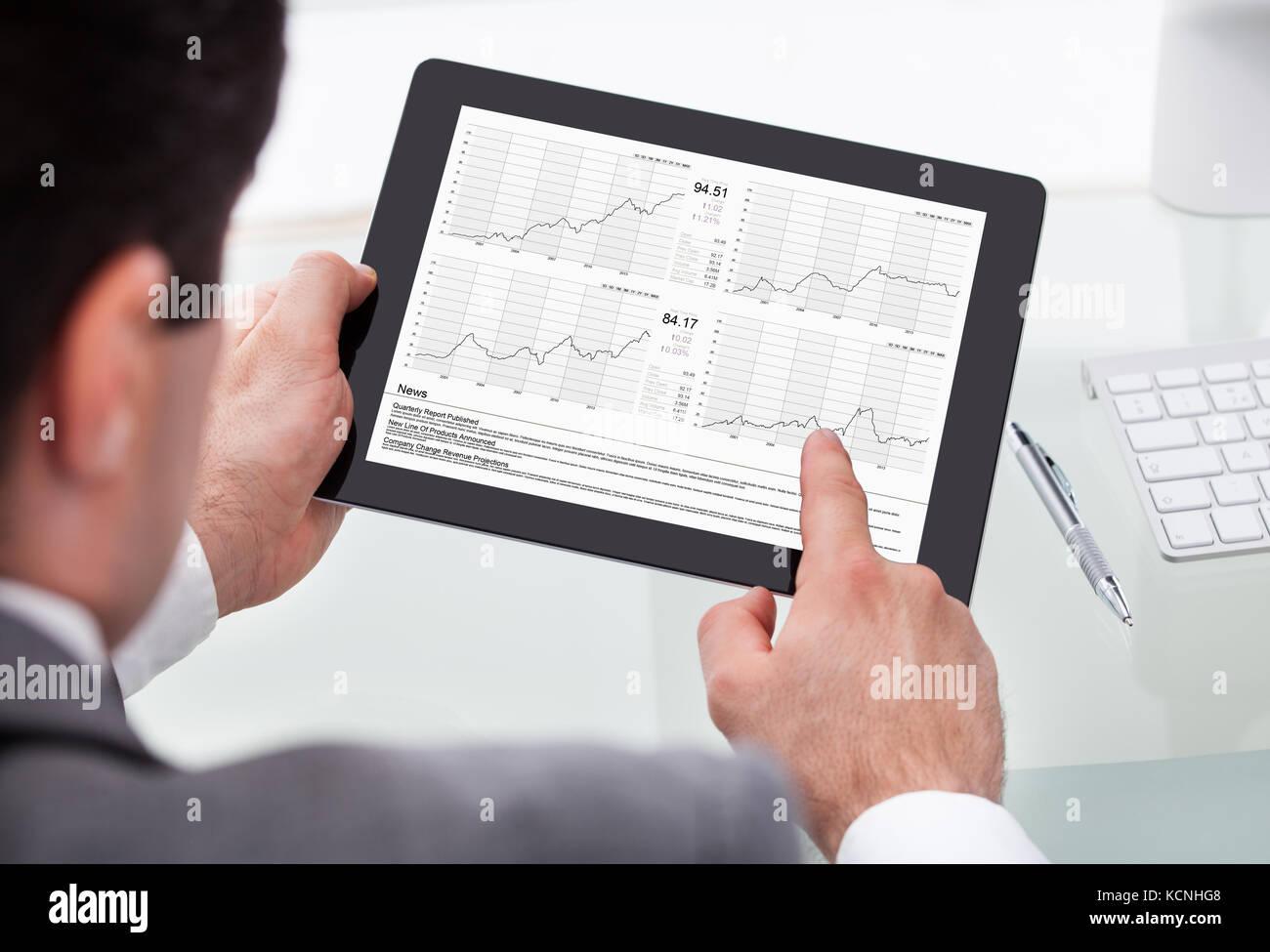 Close-up Of Businessman Analyzing Stock Market Status On Digital Tablet - Stock Image