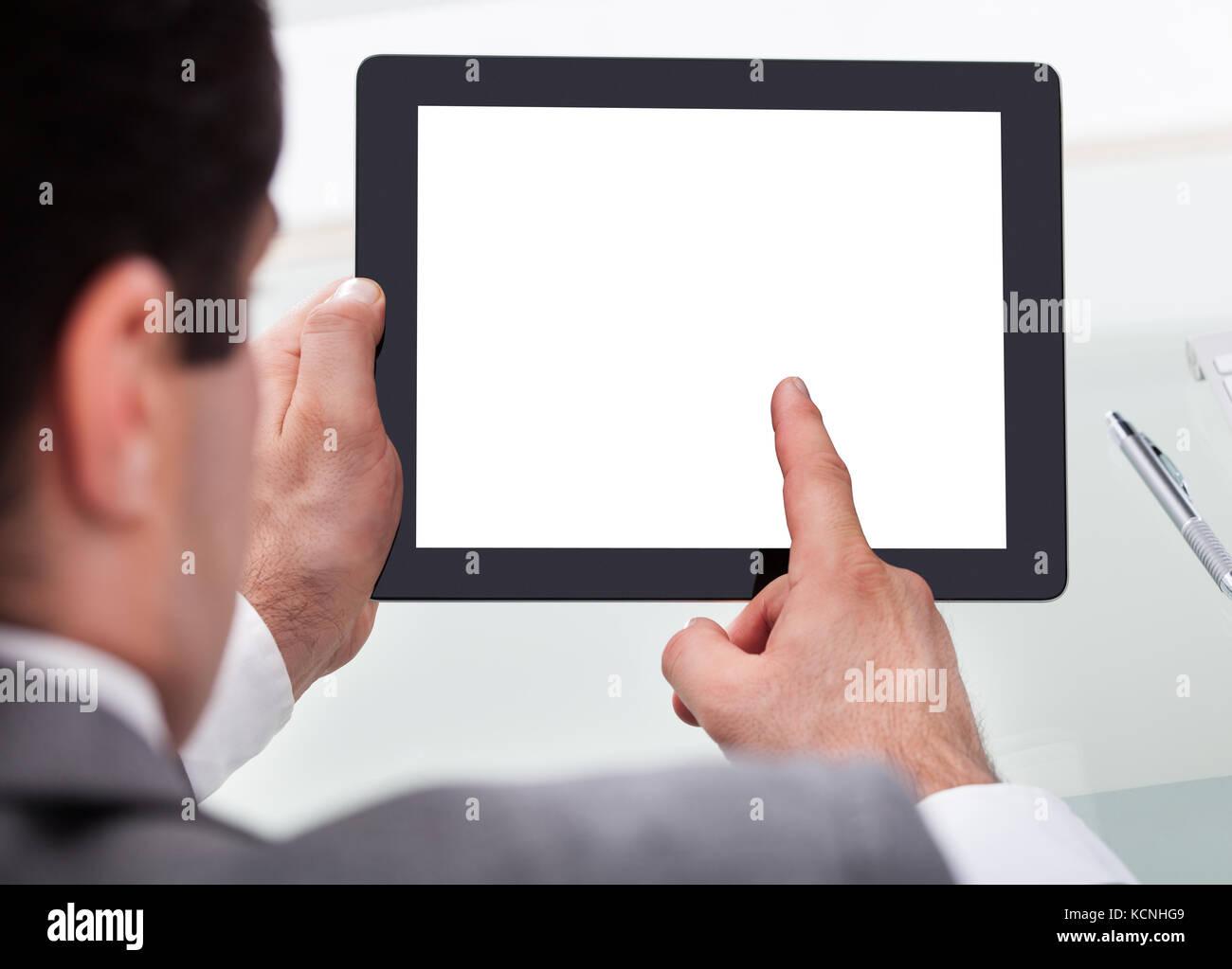 Close-up Of A Businessman Holding Digital Tablet On Desk - Stock Image