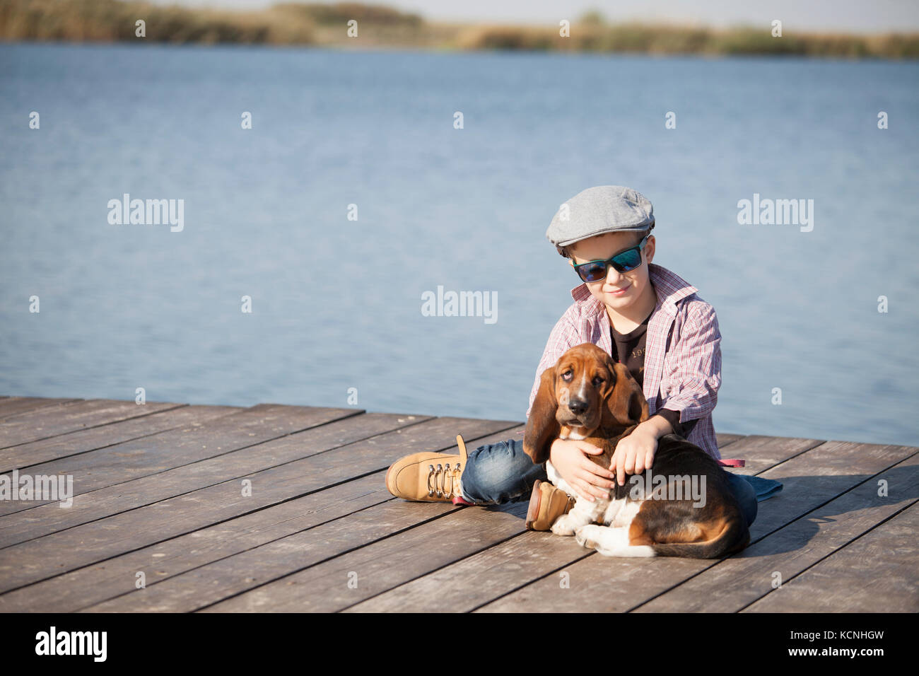 Little cute boy is sitting by the river with his dog. They enjoy together on a beautiful sunny day. Boy hugging - Stock Image