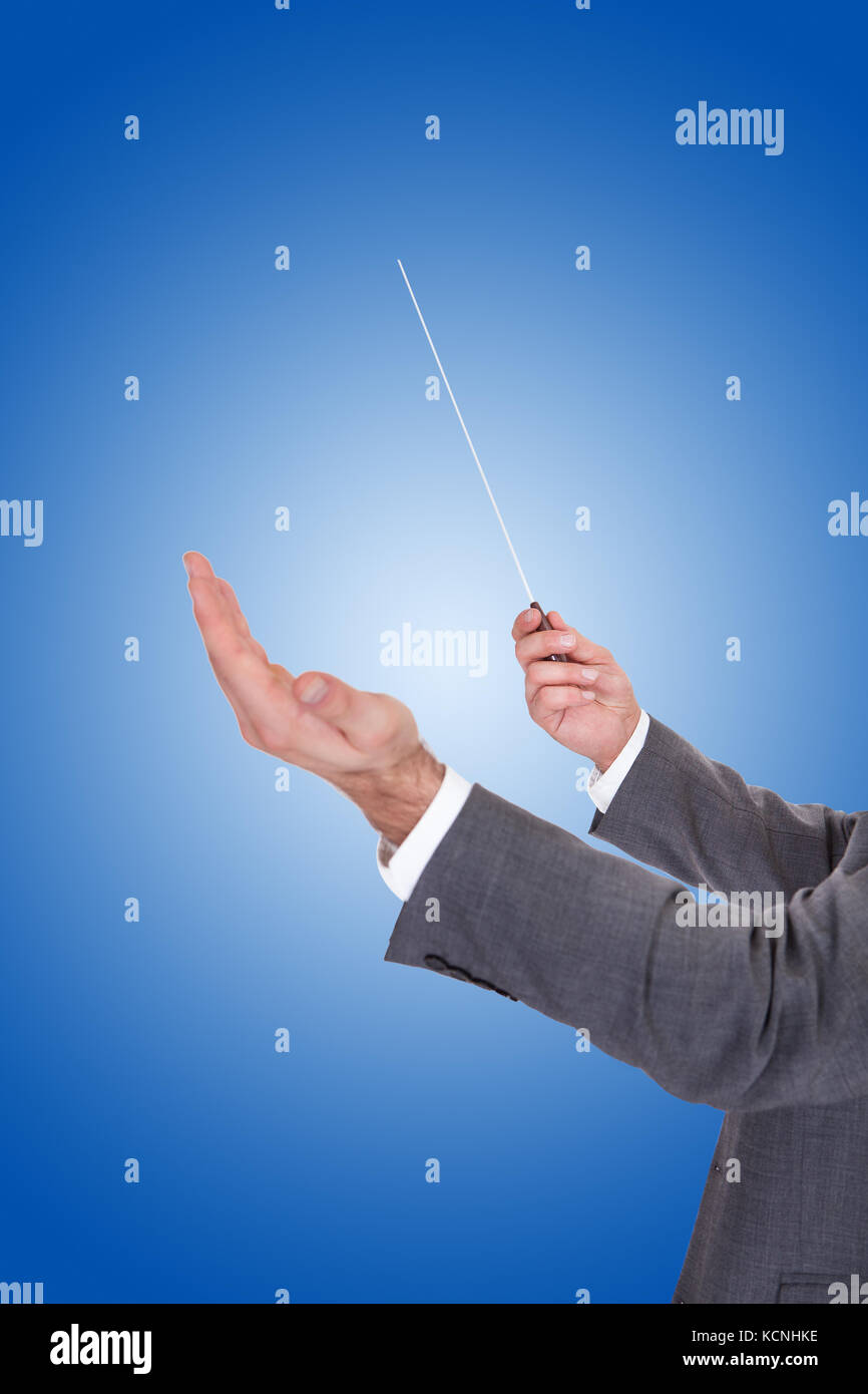 Close-up Of A Person Directing With A Conductor's Baton On Blue Background - Stock Image