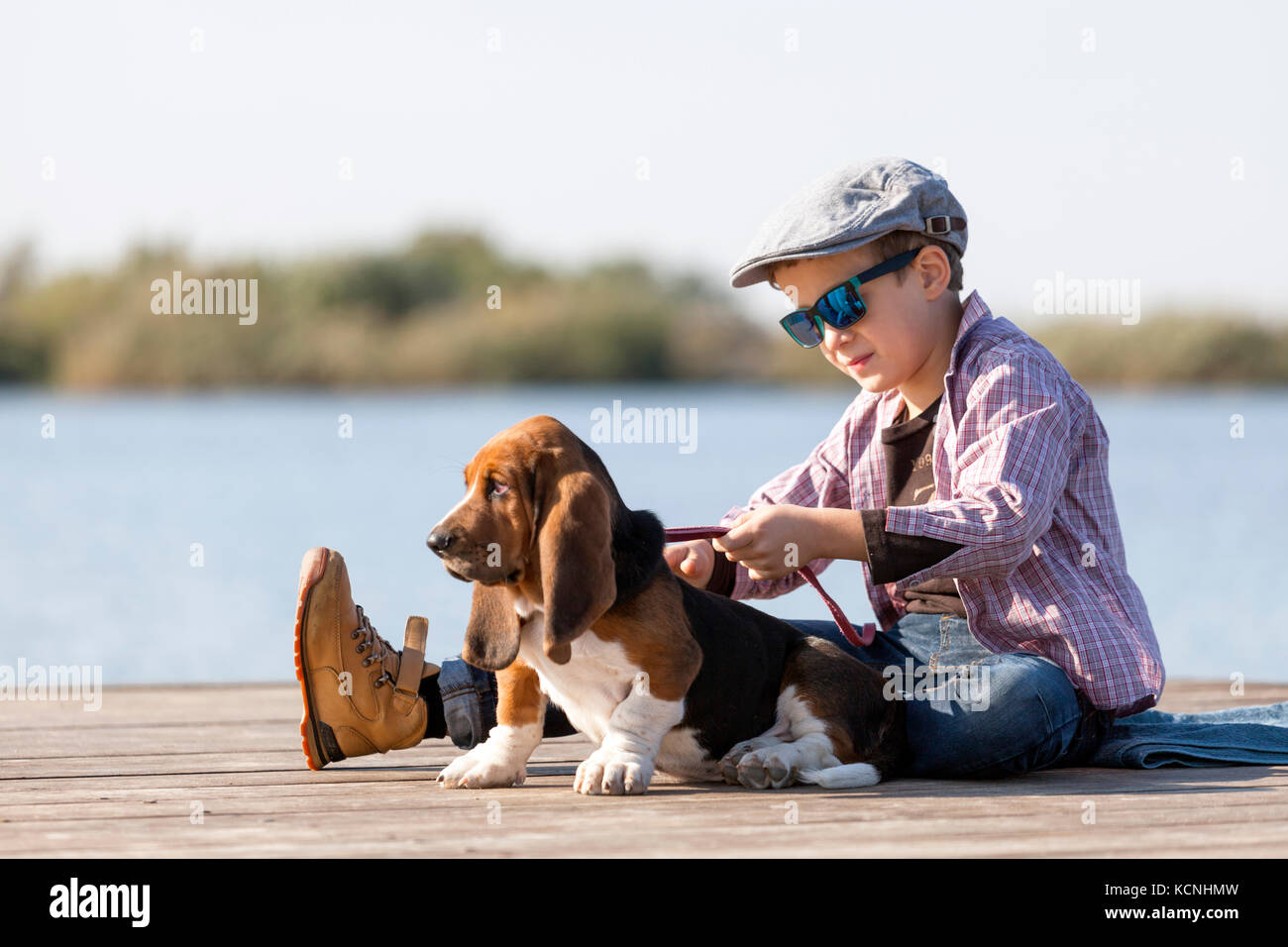 Little sweet boy with a hat and sunglasses sits by the river with his dog. They enjoy together on a beautiful sunny - Stock Image